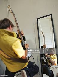 playing guitar in front of a mirror