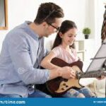 Learning to play guitar from a private guitar teacher